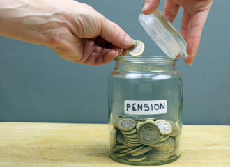 Pound coin being put into jar marked pension
